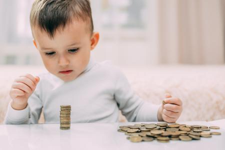 Junge schaut sich Geldstapel an, die auf einem Tisch liegen