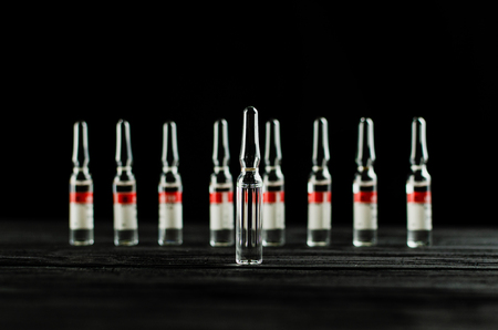 Ampoules with medicine on a black background and a wooden table with red labels