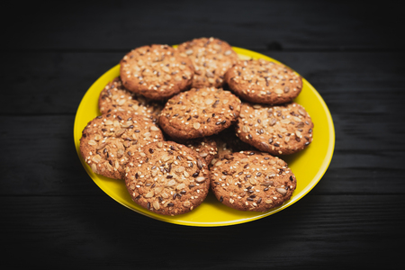 Oatmeal cookies with seeds and sesame seeds on a yellow plate, on a black wooden background