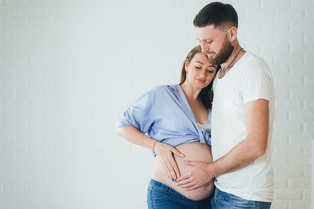 a pregnant girl is hugged by her husband at the girl's bare stomach
