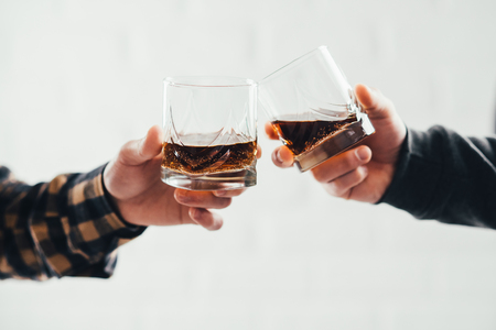 Two hands clink glasses of whiskey on a white brick background Imagens