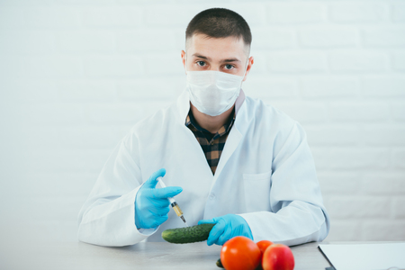 Bio Chemist in lab coat and gloves injecting nitrates and GMO in tomato on white background in lab