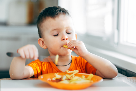 beautiful baby in orange t-shirt with orange plate eating fried French fries Stock Photo