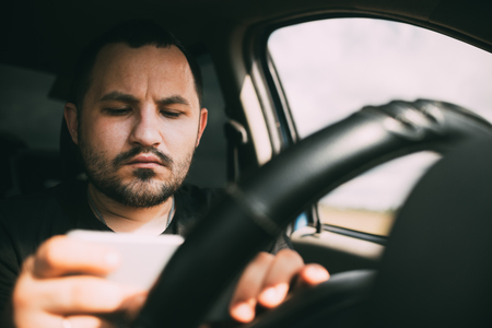 a man driving a car distracted by a smartphone