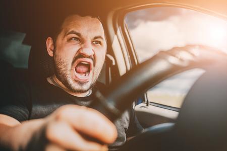 Un jeune homme au volant d'une voiture en état de choc crie de peur d'un accident