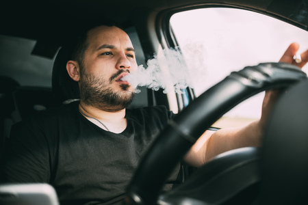 driving with a cigarette in hand, a man Smoking behind the wheel