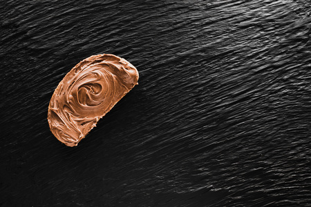 a piece of Bread smeared with chocolate paste, on a black textured background like mica, a copyspace