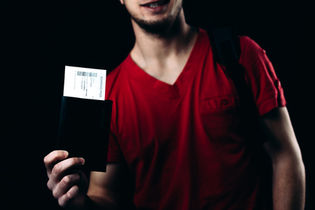 A man in a red t-shirt with air tickets and passport on a black background