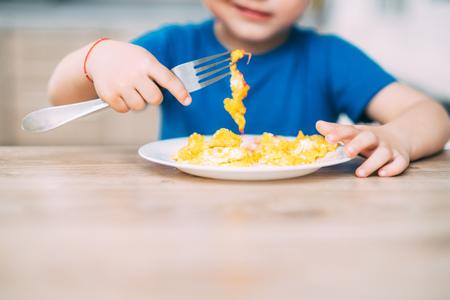 Ein Kind in einem T-Shirt in der Küche isst ein Omelett, eine Gabel