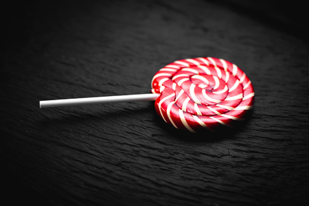 red, round colored Lollipop on black background Banque d'images