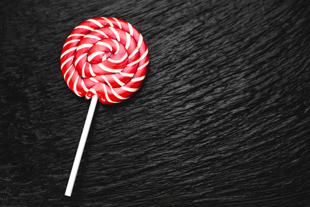 red, round colored Lollipop on black background Фото со стока