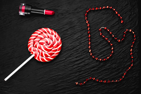 red round Lollipop on black background with texture near lipstick and beads of red color