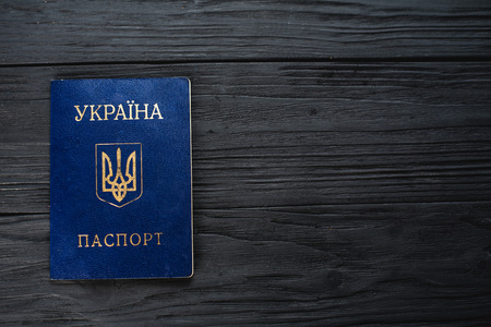 passport of Ukraine on a black wooden background copy space