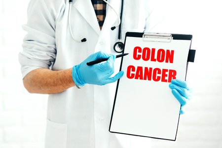 Doctor with clipboard on a white background with a pen shows the name of the disease COLON-CANCER