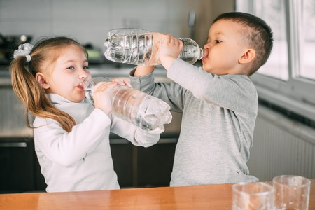 Children girl and boy drink water from liter bottles very greedily, thirsty