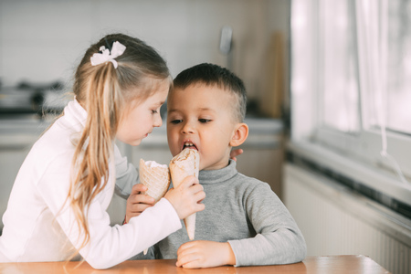 children, boy and girl eating ice cream cone in the kitchen are very fun to share with each other