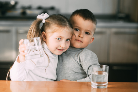 Children boy and girl in the kitchen drinking water from glasses, hugging and smiling Stock fotó