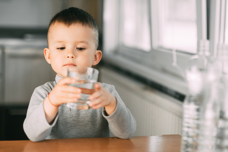 Portrait of a boy drinking a glass of water,happy in the kitchen Stock fotó