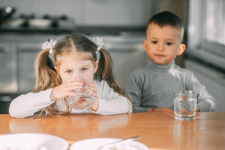 Children boy and girl in the kitchen drinking water from glasses