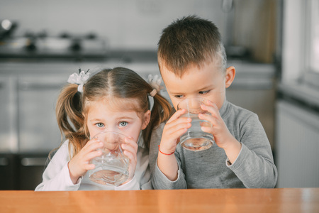 Children boy and girl in the kitchen drinking water from glasses 版權商用圖片 - 126439930