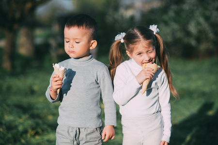 Kids Boy and girl eating ice cream outdoors on grass and trees background