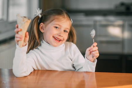 The girl in the kitchen eating the ice-cream cone with a spoon the light of day Stock Photo