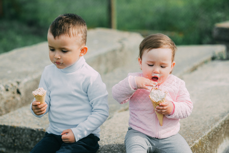 Little kids brother and sister eating ice cream outdoors in the village