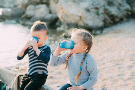 Los niños, hermano y hermana en el mar beben vasos de plástico azul de agua o jugo contra el mar y las rocas