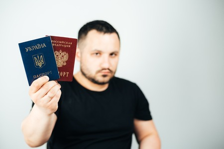 A man with a beard holding a passport of Russia and Ukraine