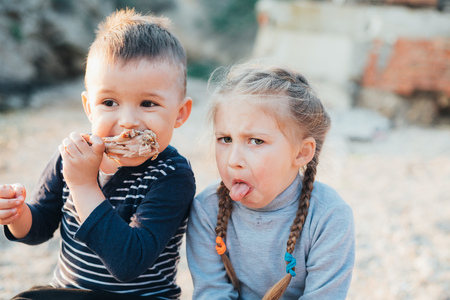 Children, brother and sister have fun eating chicken Shin on the beach near the sea and rocks, very appetizing Archivio Fotografico - 126440457