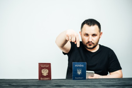 A man with passports of Ukraine and Russia points his finger at the passport of Ukraine