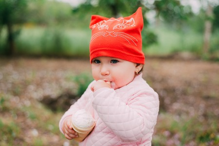 little girl in the garden in a red hat eating ice cream in a waffle Cup