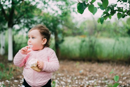 little girl in the garden on the background of greenery and trees very cute eating ice cream finger in a waffle Cup dirty face
