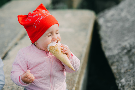 Little girl outdoors in the village eating ice cream very greedily Archivio Fotografico