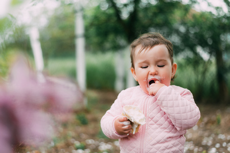 little girl in the garden on the background of greenery and trees very cute eating ice cream in a waffle Cup dirty face