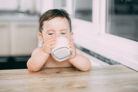 A little girl in the kitchen drinking milk, milkshake or yogurt from a glass is very appetizing and greedy