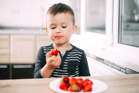 Little boy in the kitchen eating fresh strawberries very appetizing and tasty Archivio Fotografico