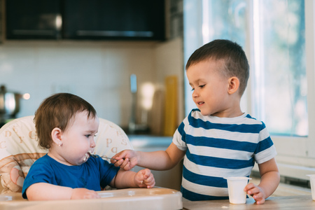 Kids in the kitchen, brother feeds baby sister yogurt with a spoon