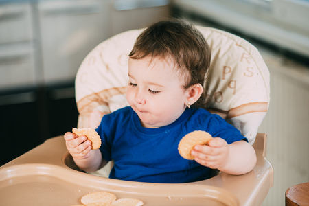 Little girl in a high chair eating round biscuits with pleasure
