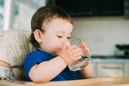 Een klein meisje in de keuken in de middag in een kinderstoel drinkwater