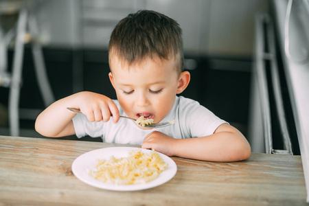 ein kleiner Junge isst nachmittags in der Küche alleine Nudeln in Form einer Spirale sehr appetitlich
