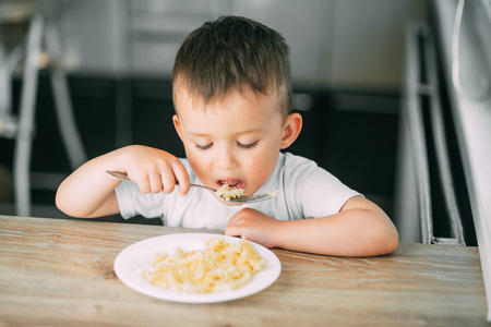 un petit garçon mange des pâtes en forme de spirale l'après-midi dans la cuisine tout seul très appétissant