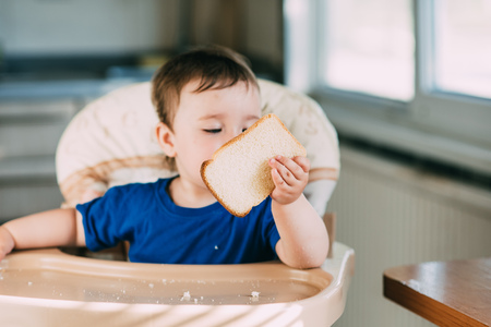 Baby girl is very greedy eating a piece of white bread, hungry and happy Reklamní fotografie