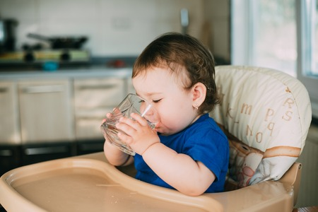 A little girl in the kitchen in the afternoon in a high chair drinking water Stock Photo