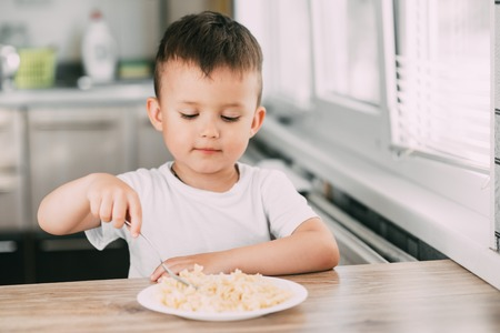 a child in the kitchen during the day eating pasta in a spiral in a white t-shirt at the table Stock Photo