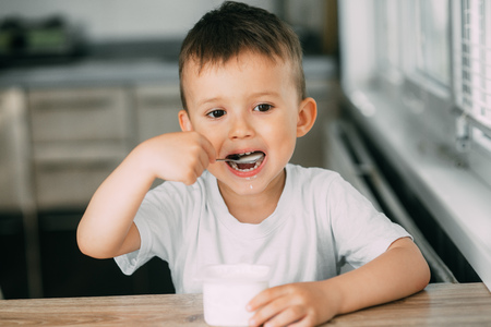 Lovely little boy eating yogurt in the kitchen during the day very appetizing 免版税图像