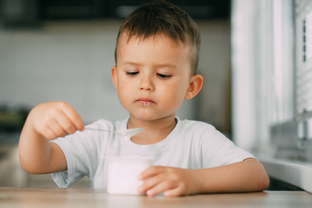 Lovely little boy eating yogurt in the kitchen during the day very appetizing