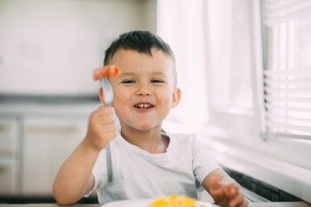 a child in a t-shirt in the kitchen eating a sausage and an omelet with a fork is very tasty