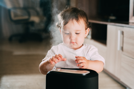 The baby looks at the humidifier. The concept of humidity in the home and health Stok Fotoğraf
