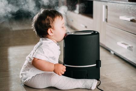 El bebé mira el humidificador. El concepto de humedad en el hogar y salud. Foto de archivo